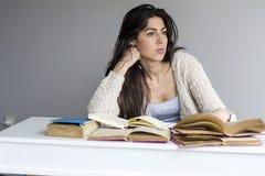 Giovane donna stanca e preoccupata che studia per gli esami Fotografia Stock
