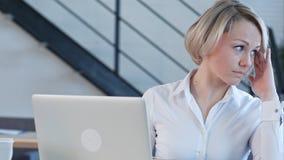 Giovane donna stanca nell'ufficio che lavora con un computer portatile e che fissa allo schermo di computer Immagini Stock Libere da Diritti