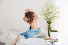 Giovane donna stupefacente che si siede all'interno sull'allungamento del letto Immagini Stock