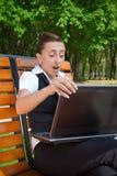 Giovane donna stupita con il computer portatile che si siede sul banco Fotografie Stock