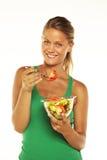 Giovane donna su priorità bassa bianca con un'insalata Immagini Stock