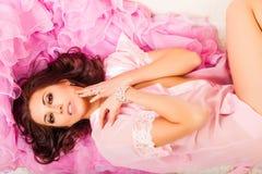 Giovane donna su un capo rosa Fotografia Stock