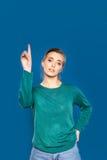 Giovane donna su un dare segni blu del fondo Fotografia Stock