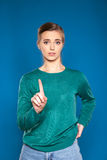 Giovane donna su un dare segni blu del fondo Fotografia Stock Libera da Diritti