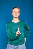 Giovane donna su un dare segni blu del fondo Immagini Stock Libere da Diritti