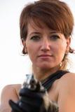 Giovane donna su un fondo bianco per tendere una pistola fotografie stock