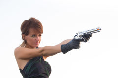 Giovane donna su un fondo bianco per tendere una pistola fotografia stock libera da diritti