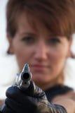 Giovane donna su un fondo bianco per tendere una pistola immagini stock