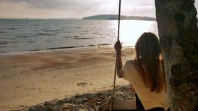 Giovane donna su un'oscillazione su una spiaggia tropicale al rallentatore archivi video