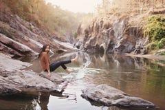 Giovane donna su una banca di fiume che gioca con acqua Immagini Stock