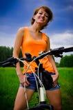 Giovane donna su una bicicletta all'estate Immagini Stock