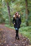 Giovane donna su una passeggiata isolata della foresta fotografia stock