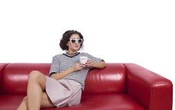 Giovane donna su uno strato che posa con una tazza di caffè Fotografie Stock Libere da Diritti