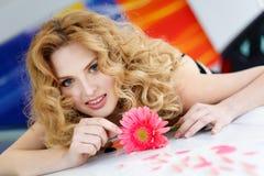Giovane donna sul cappuccio di nuova automobile con il fiore e l'animale domestico Fotografie Stock
