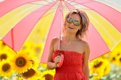 Giovane donna sul giacimento di fioritura del girasole fotografia stock libera da diritti