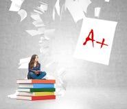 Giovane donna sul mucchio dei libri con il volo di carta intorno Fotografia Stock Libera da Diritti