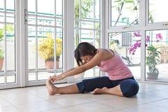 Giovane donna sul pavimento che fa allungando esercitazione Immagini Stock Libere da Diritti