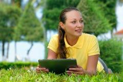 Giovane donna sul prato inglese sotto una palma con il suo comput della compressa Fotografie Stock Libere da Diritti