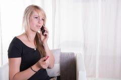 Giovane donna sul telefono che mangia i dolci Fotografie Stock Libere da Diritti