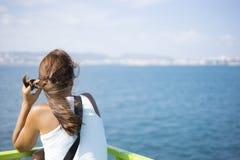 Giovane donna sul traghetto che guarda verso la sua destinazione immagine stock libera da diritti
