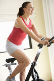 Giovane donna sulla bici di esercitazione Fotografia Stock