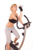 Giovane donna sulla bicicletta di esercitazione Fotografia Stock