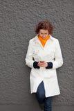 Giovane donna sulla parete che esamina il telefono delle cellule immagini stock libere da diritti