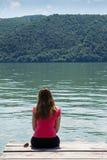 Giovane donna sulla riva del fiume fotografia stock