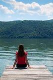 Giovane donna sulla riva del fiume fotografia stock libera da diritti