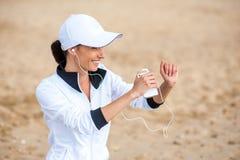 Giovane donna sulla spiaggia che ascolta la musica Immagini Stock