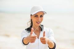 Giovane donna sulla spiaggia che ascolta la musica Fotografia Stock