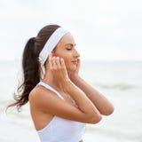 Giovane donna sulla spiaggia che ascolta la musica Fotografie Stock