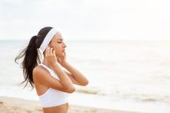 Giovane donna sulla spiaggia che ascolta la musica Fotografia Stock Libera da Diritti