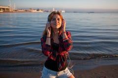Giovane donna sulla spiaggia che ascolta la musica, con le cuffie, il mante della musica sulla spiaggia Fotografie Stock Libere da Diritti