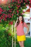 Giovane donna sulla vacanza di estate vicino ai fiori esotici Immagine Stock