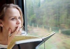 Giovane donna sulle note di una scrittura del treno Immagini Stock Libere da Diritti