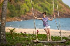 Giovane donna sulle oscillazioni di legno sulla spiaggia del mare fotografia stock