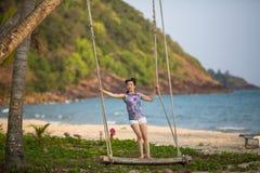 Giovane donna sulle oscillazioni di legno sulla spiaggia del mare immagini stock