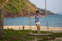 Giovane donna sulle oscillazioni di legno sulla spiaggia del mare immagine stock libera da diritti