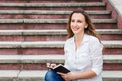 Giovane donna sulle scale e sulle note di fabbricazione in taccuino Immagine Stock