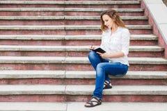 Giovane donna sulle scale e sulle note di fabbricazione in taccuino Fotografia Stock Libera da Diritti