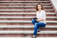 Giovane donna sulle scale e sulle note di fabbricazione in taccuino Immagine Stock Libera da Diritti