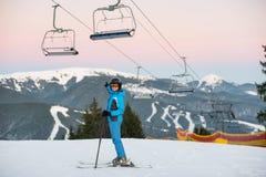 Giovane donna sullo sci che sorride e che mostra mano alla distanza Immagine Stock Libera da Diritti