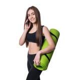 Giovane donna sveglia in abiti sportivi con la stuoia verde pronta per l'allenamento Sorridendo e parlare sul telefono Isolato su Fotografia Stock Libera da Diritti