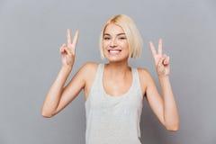 Giovane donna sveglia allegra che mostra il segno di pace con entrambe le mani Fotografie Stock Libere da Diritti
