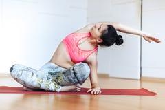 Giovane donna sveglia che allunga e che si scalda prima del risolvere ad un'yoga immagini stock