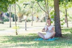 Giovane donna sveglia che allunga nel parco Fotografie Stock Libere da Diritti