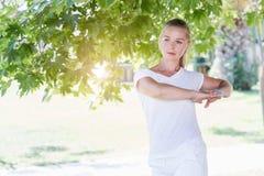 Giovane donna sveglia che allunga nel parco Fotografie Stock