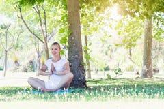 Giovane donna sveglia che allunga nel parco Immagine Stock Libera da Diritti