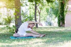 Giovane donna sveglia che allunga nel parco Immagine Stock